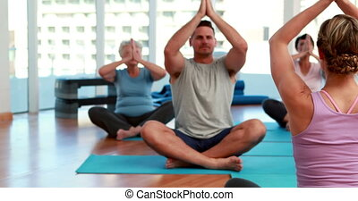 Yoga class sitting in lotus position together at the gym