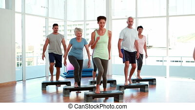 Aerobics class stepping together at the gym