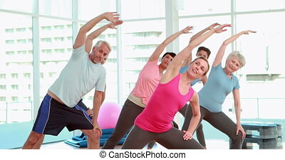 Aerobics class stretching their arms together at the gym