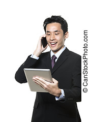 Asian businessman talking on phone with a tablet computer -...