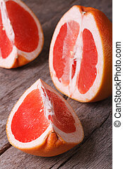 large pieces of red grapefruit on the old wooden table...
