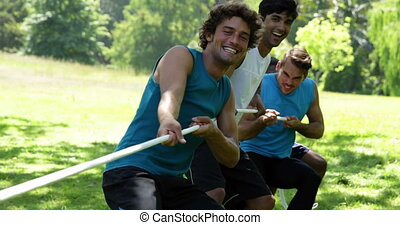 Men pulling a rope in a tug of war on a sunny day