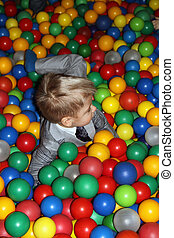Baby boy playing in playground colourful ball pool