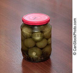Jar of pickled physalis on a wooden background