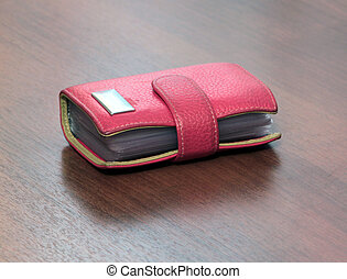 red case for visiting cards isolated on wooden desk...