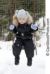 Active little boy has fun in playground on a snowy winter...