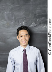 Chinese business man standing next to a blackboard.