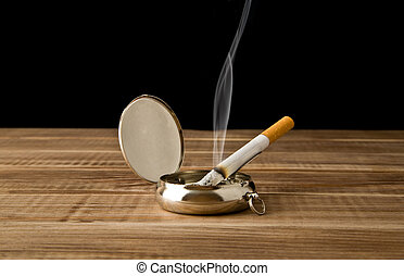 cigarette in an ash-tray on a black background