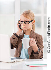 Little businesswoman. Confident little girl in glasses and formalwear talking on the phone while sitting at the table and looking at laptop