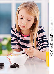 I am not hungry. Sad little girl eating something from the...