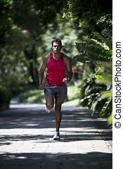 Athletic Indian man running in park. Asian Runner jogging...