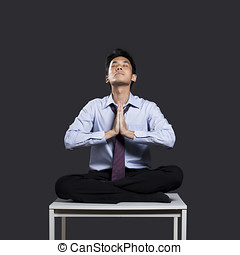 Chinese Businessman on desk in yoga position. - Asian...
