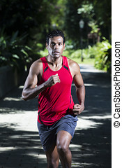 Close up of an athletic Indian man running in park -...
