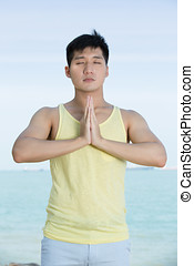 Asian Man doing yoga on a beach.