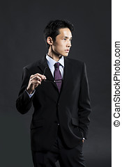 Stylish Chinese business man. In front of dark background -...