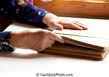 Elderly Reading - An old pair of hands holding the pages in...