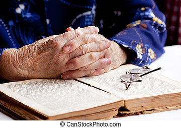 Hands Praying - An old pair of hands in prayer on a book