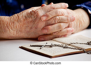 Old Faith - Old female hands with a cross and book