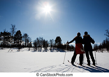 Winter Ski Holiday - Two women in a winter landscape cross...