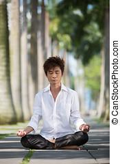 Asian business man meditating.