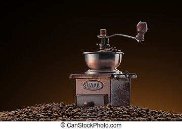 Retro manual coffee mill on roasted coffee beans