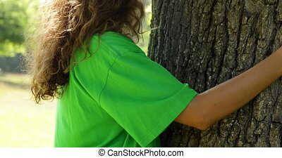 Environmental activist hugging a tree on a sunny day