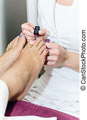 Pedicurist at Beauty Salon - Girl toe nails being pedicured...