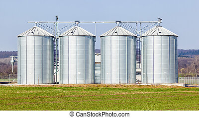 silver silos in field - four silver silos in field under...