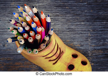 Many colored pencils in a ceramic boot with wooden...