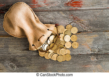 Dollar coins spilling out of a drawstring pouch - Pile of...