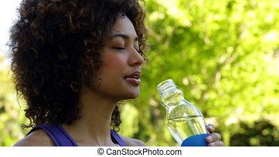 Smiling fit brunette taking a drink