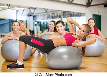 smiling female instructor with fitness ball - fitness, gym,...