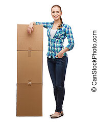 young woman standing next to tower of boxes - happiness,...