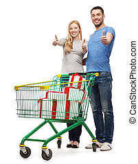 smiling couple with shopping cart and gift boxes -...