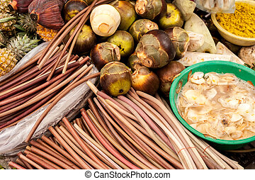 Exotic tropical fruits and vegetables at traditional asian food market. Mangosteen, water lilly stems, marinated mushrooms, pineapples and curry