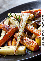 Roasted Root Vegetables - Roasted root vegetables on a black...