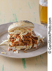 Pulled pork in a bun with a beer on the side
