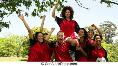 Female football team celebrating a win in the park on a...
