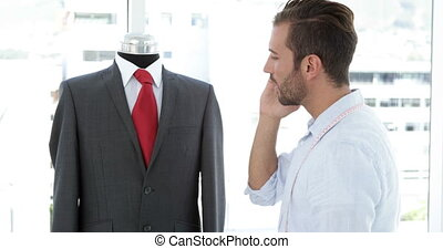 Handsome tailor touching suit and talking on phone in his...