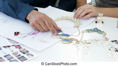 Design team looking at costume jewelry and talking in their...