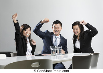 Happy Chinese business people celebrating in a meeting. -...