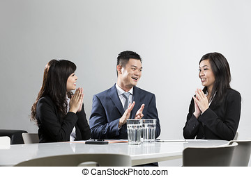 Happy Chinese business people applauding in a meeting....