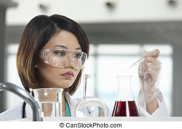 Woman scientist analyzing a solution - An Chinese scientific...