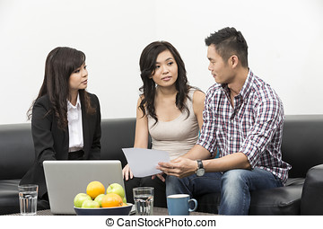Finance Consultant showing investment plans to Asian couple...