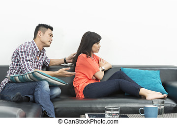 Angry Chinese couple having an argument in their living room