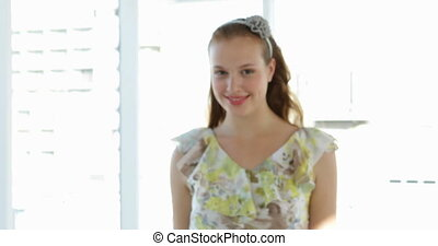 Model in floral dress walking towards camera and smiling in...