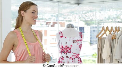 Smiling fashion designer looking at camera in her studio