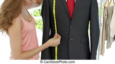 Smiling fashion designer measuring suit on mannequin in her...