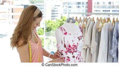 Smiling fashion designer looking at camera adjusting dress...