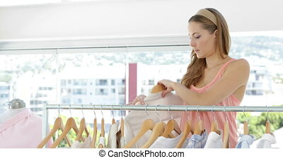 Attractive fashion designer looking through clothing rail in...